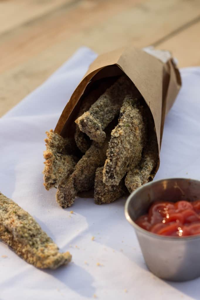 Brown bag of portobello baked fries with a side of ketchup