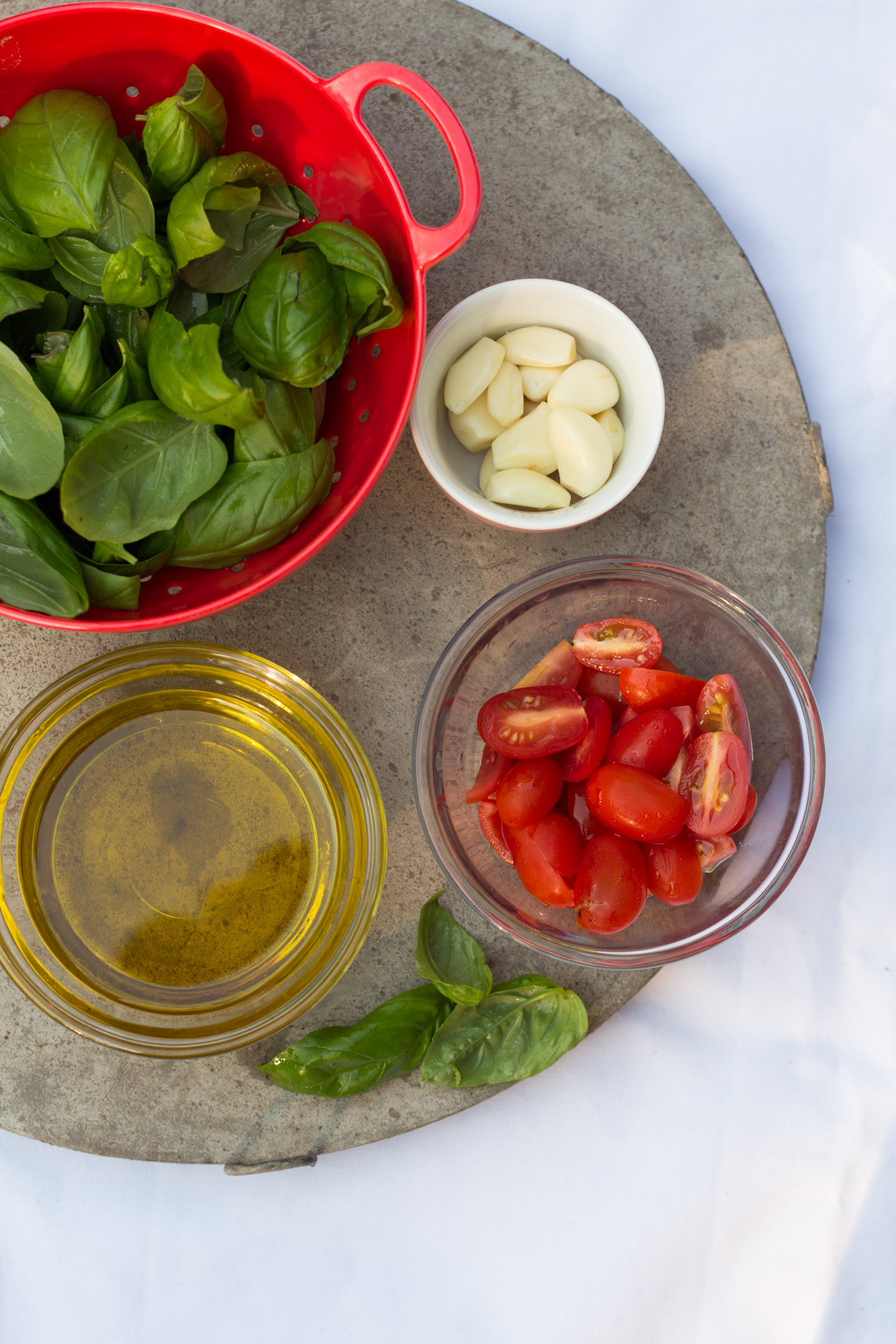 Ingredients (garlic, basil, tomato, olive oil) on a tray to make pistou paste