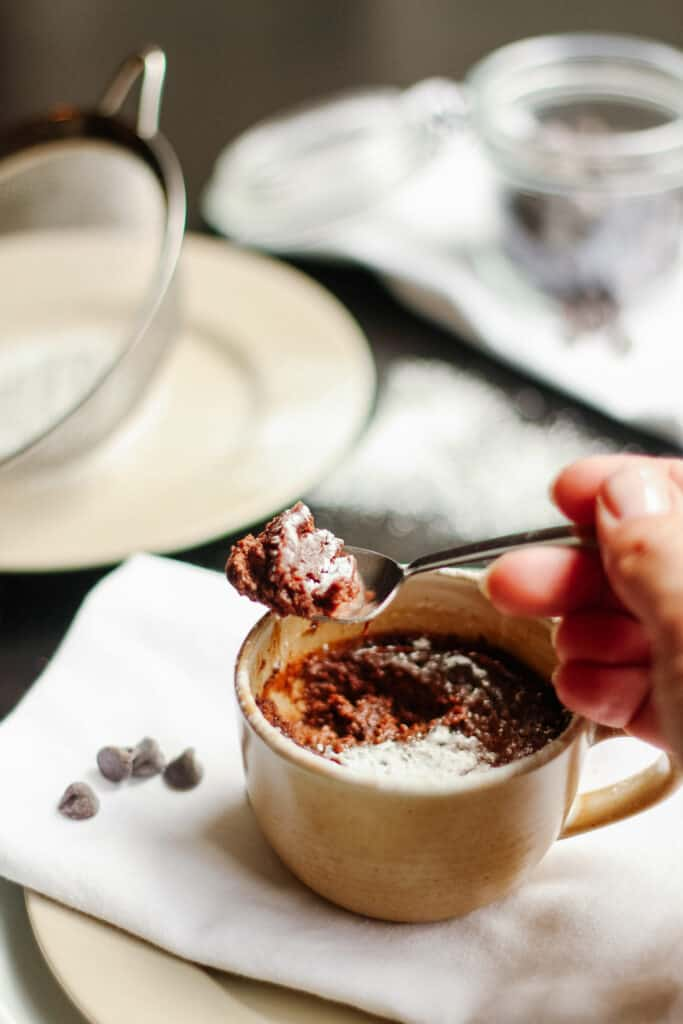 Cup with chocolate pot de creme, spoon with some creme.