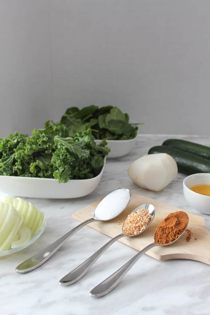 Flatlay of ingredients for the green soup. Spinach, kale, zucchinis, parsnip, onions.