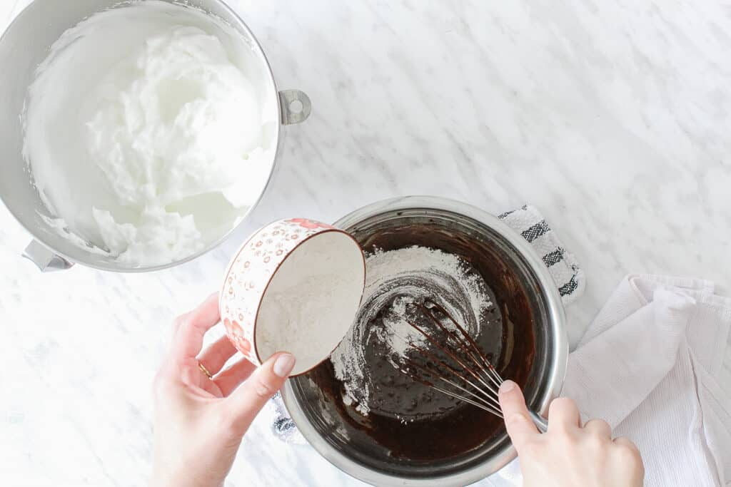 Egg whites beaten and flour being poured in the chocolate batter