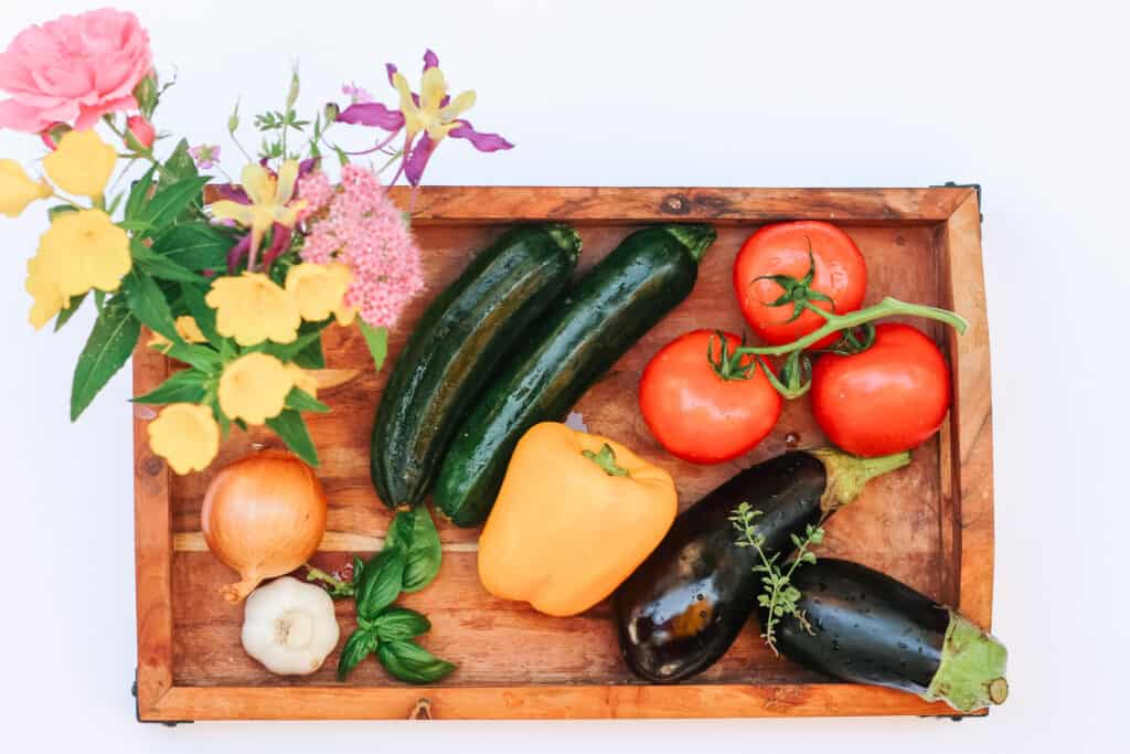 Wooden tray with a bouquet of flowers and different vegetables for the easy French Ratatouille: 3 tomatoes, 2 zucchinis, yellow pepper, onion, garlic