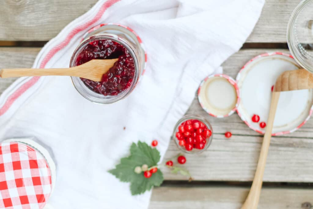 View from above of red currant jam with white dish towel and wood background