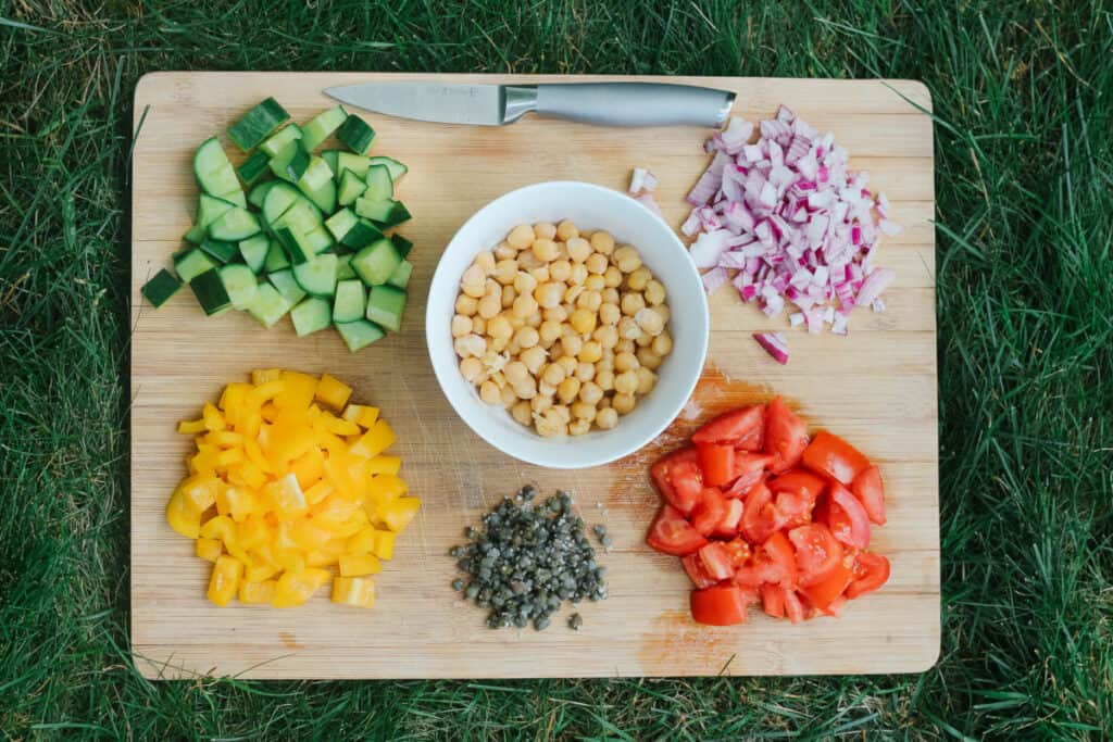 Cutting board with a knife and vegetables cut for the mediterranean salad