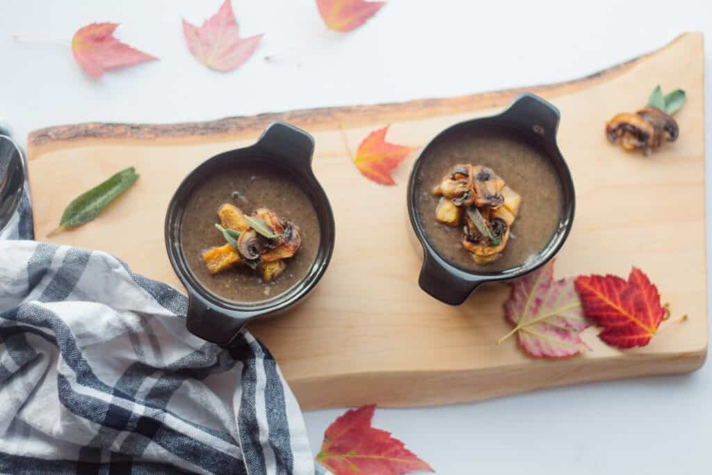 Dairy free sage mushroom soup in 2 individual black cocottes with fall leaves around