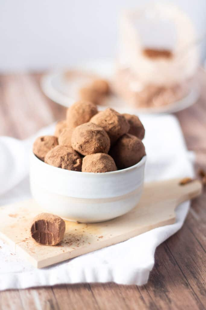 Bowl of homemade truffles in a white bowl with one bitten on the side