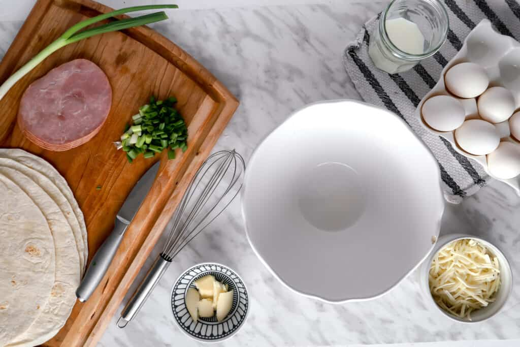 Mise en place with eggs, ham, scallions on a wooden board.