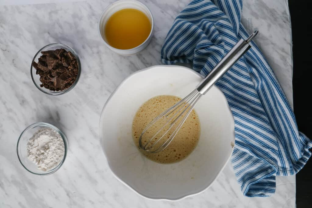 White bowl with a whisk and ramekins and ingredients around. Blue towel dish on the side