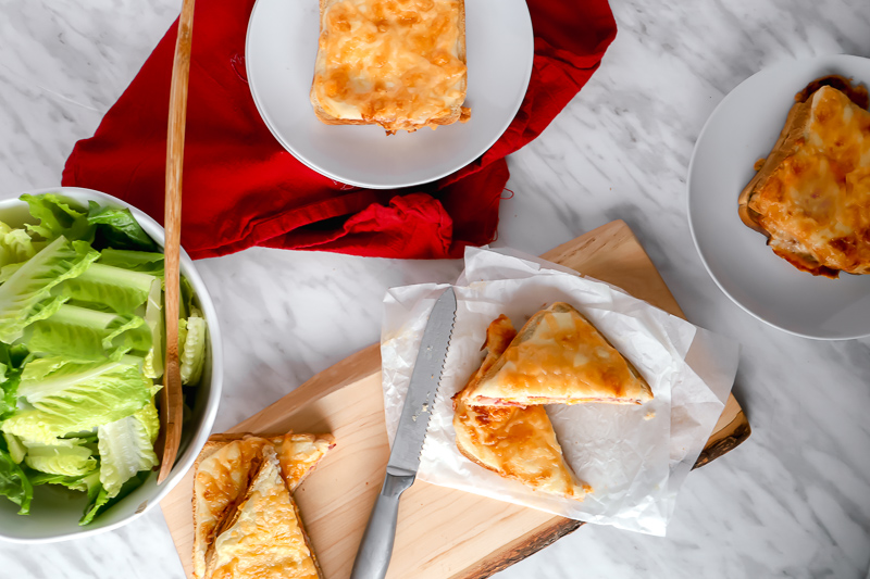 Top view of croque-monsieur sandwiches, sliced on a wooden board and whole in white plates.