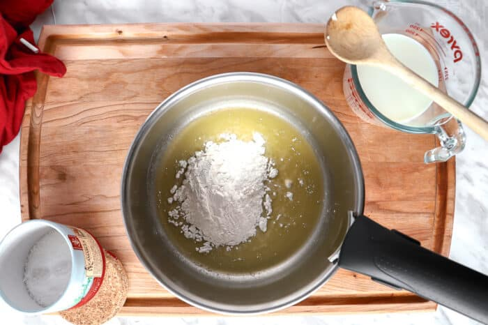 Flour on a melted butter with a wooden spoon on the side
