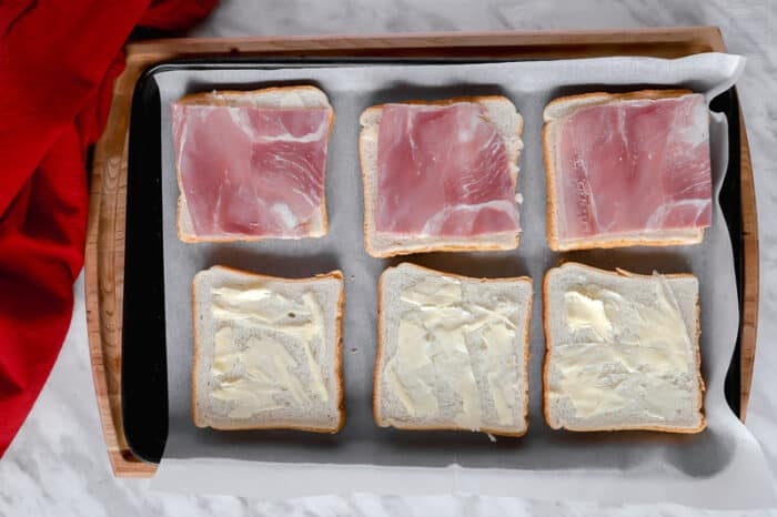 Top view of buttered bread and ham on a baking sheet