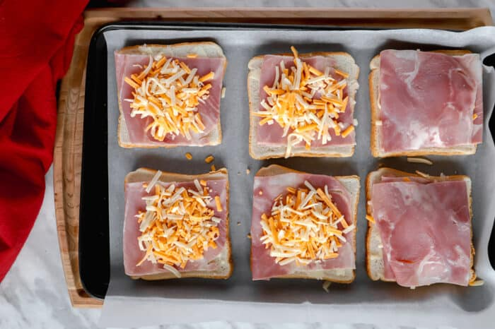 Top view of cheese on ham and bread on a baking sheet