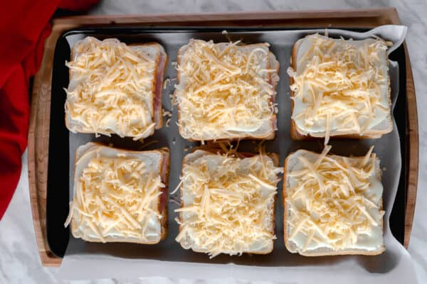 Top view of unbaked croque-monsieur sandwiches on a baking sheet.