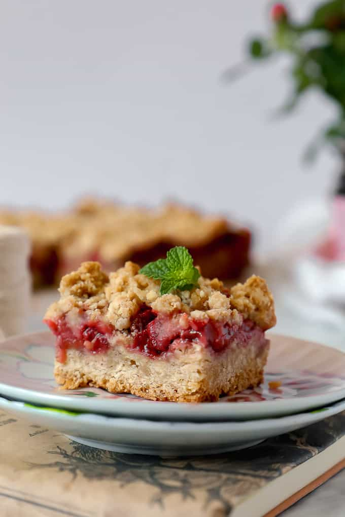 Close up of a strawberry crumble bar on a small plate on an old book. A small leaf of mint is on top.