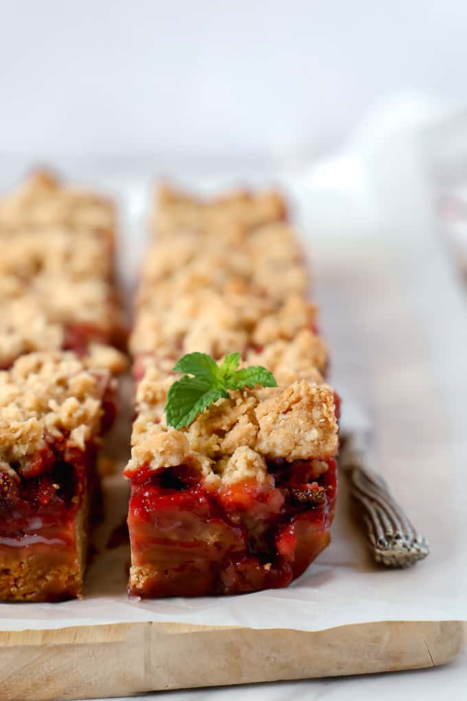 Side close of a strawberry crumble bar with a small mint leaf of top.